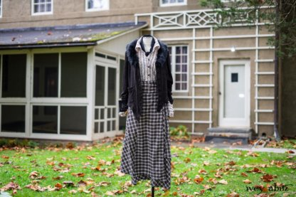 """Limited Edition Coulson Cardigan in Dignity Soutache Knit; Pierrepont Shirt in Dignity Washed Vine Silk; Fairholme Necktie in Unity Washed Linen; Fairholme Skirt in Dignity Plaid Cotton. Location: In front of Eleanor's office where she wrote many books, letters, and the newspaper column """"My Day."""" Location: Eleanor Roosevelt National Historic Site. Val-Kill, Hyde Park, New York."""