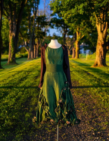 • Limited Edition Vineyard Frock in Kale Washed Silk with Hand Sculpted Floral and Vine Embellishments in a Mix of Silk, Cotton, Velvet and Antique Glass • Porte Cochere Sash in Kale Crinkled Double Gauze • Crest Jacket in Black Ethereal Stripe Knit. Bespoke clothing designed by Cynthia Ivey Abitz.