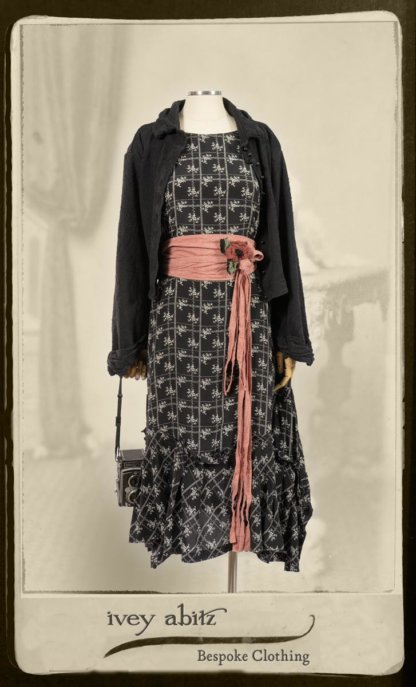 Bertie Jacket in Black Floral Raised Knit; Fairholme Frock in Black and White Washed Silk; Cilla Slip Frock in Signature Black Lightweight Linen Knit; Porte Cochere Sash in Rosy Washed Cotton; Floravinea Brooch in Rosy Washed Crinkled Linen. By Ivey Abitz.
