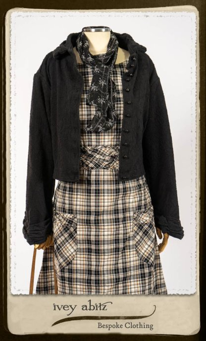 Bramley Frock in Black and White Picture Book Plaid; Clotaire Sash in White on Black Floral Silk Chiffon; Bertie Jacket in Black Floral Raised Knit; Bertie Frock in Black Puckered Check Weave. By Ivey Abitz.