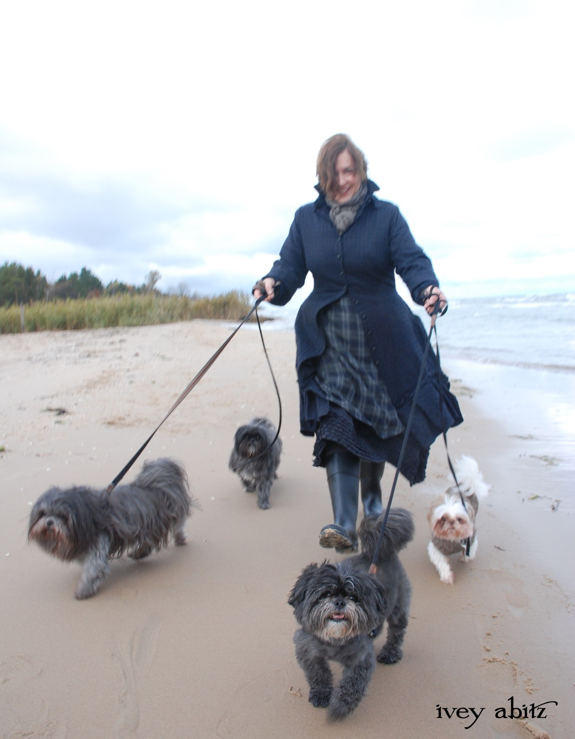 Cynthia Ivey Abitz, clothing designer, walks the beach with part of her shih tzu pack.