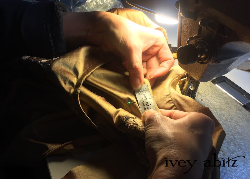 Sewing the label onto the Emmy Dress for Carolyn Hennesy, designed by Cynthia Ivey Abitz.