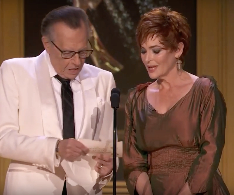 Carolyn Hennesy announcing an Emmy winner with Larry King, wearing her Ivey Abitz couture gown.