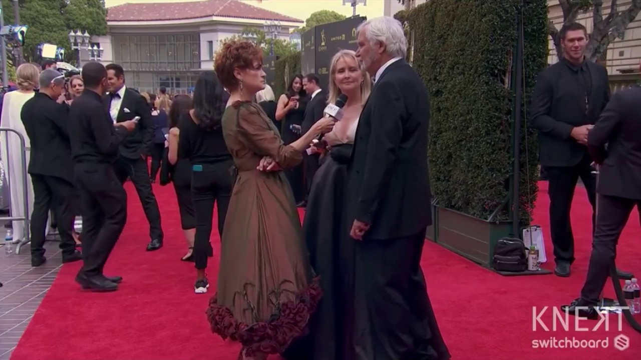 John McCook compliments Carolyn Hennesy on her Ivey Abitz dress on the red carpet.